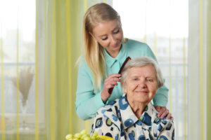young woman comb the hair of elderly woman